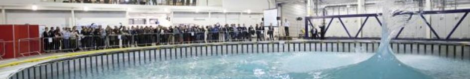 View of Flowave wave tank with conical wave formation and many spectators watching on from the side and upper levels